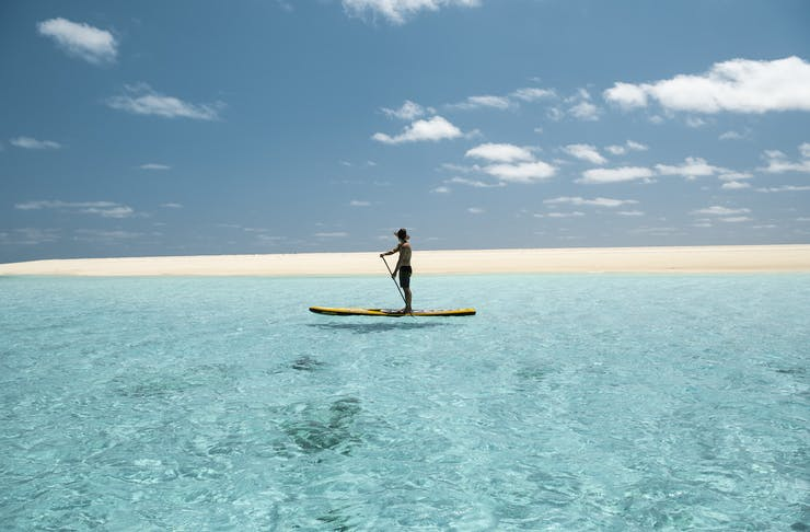 a person stand up paddle boarding at a beach near Broome
