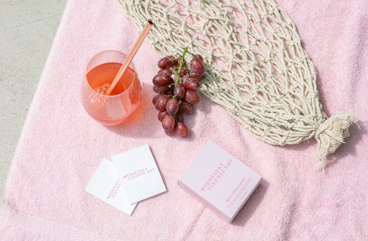 a pink drink and packets of powder on a pink towel