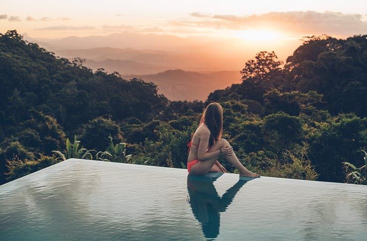 a woman sitting on the edge of an infinity pool, overlooking a sunset