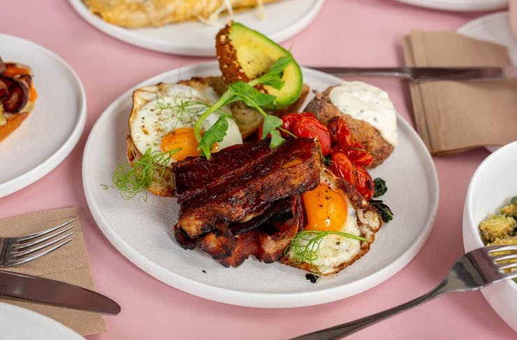 A plate of big breakfast with eggs and pork belly