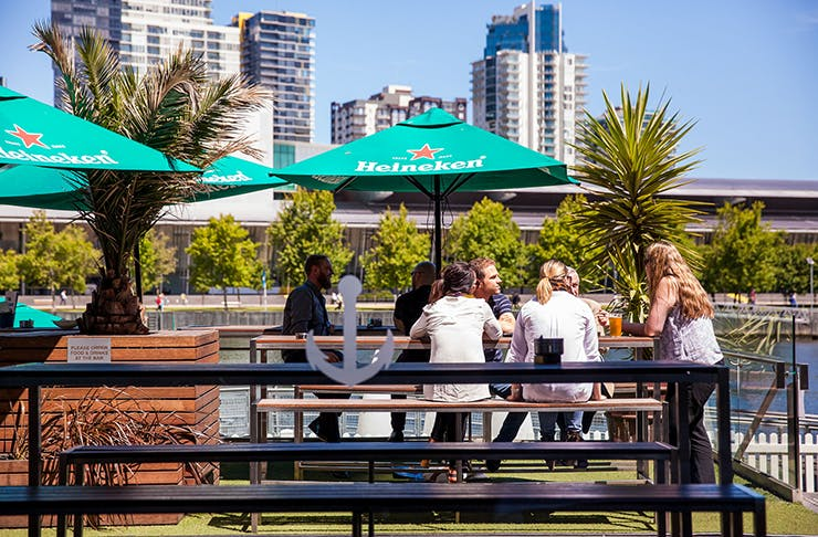 People dining at a pub by the docks of the Yarra River on a sunny day.
