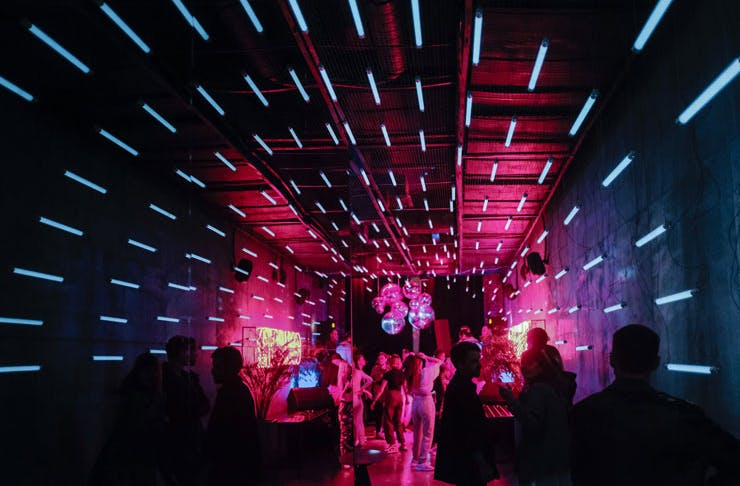 A night club with a small crowd of people dancing under blue neon lights and disco balls.