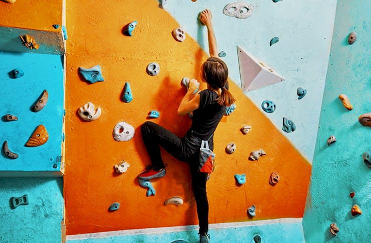 a woman climbing a rockclimbing wall