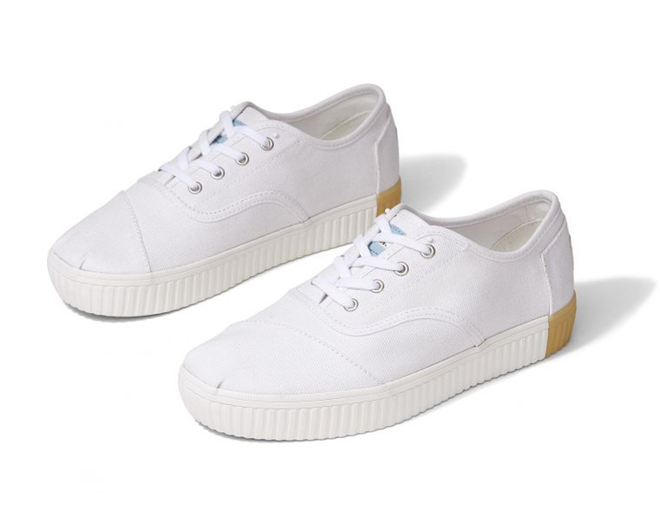 White canvas sneakers from toms, with a rubber heel.
