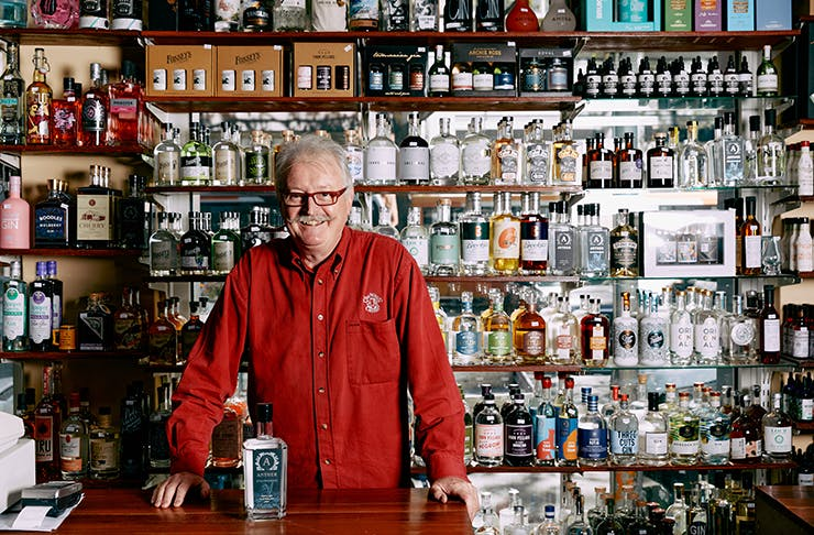 A man in a red shirt standing in front of shelves of alcohol.