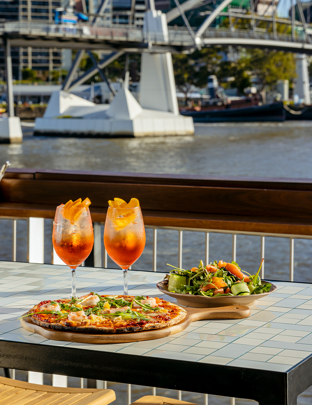 two cocktails and a pizza on a table overlooking the river