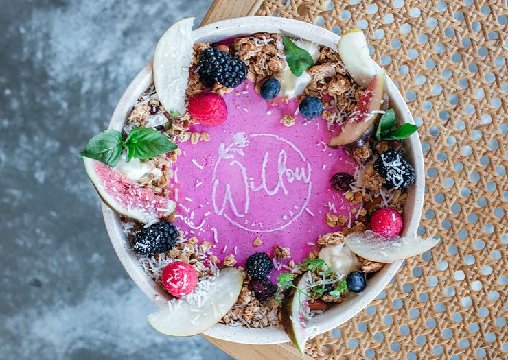 a bowl of pink panna cotta with fruit and granola seen from the top down