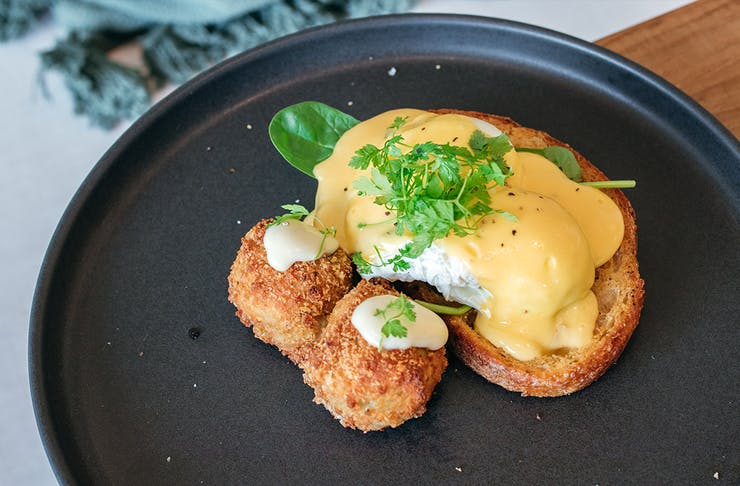 eggs benny with crab cakes alongside