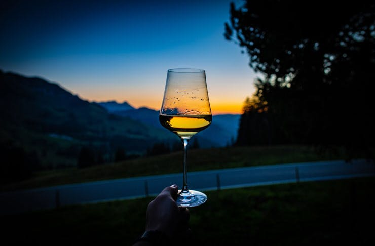 A wine glass, half filled with white wine held up against a sunset.