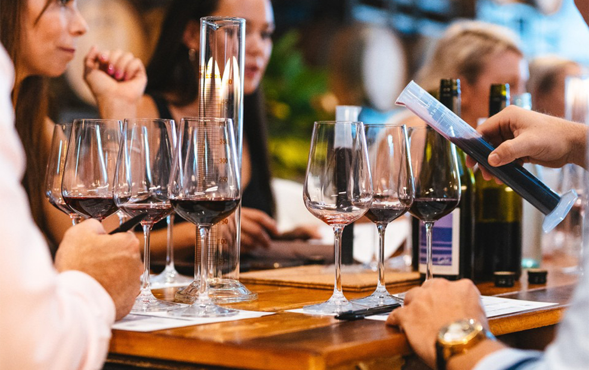 Several people at a table blending wine in glasses with beakers
