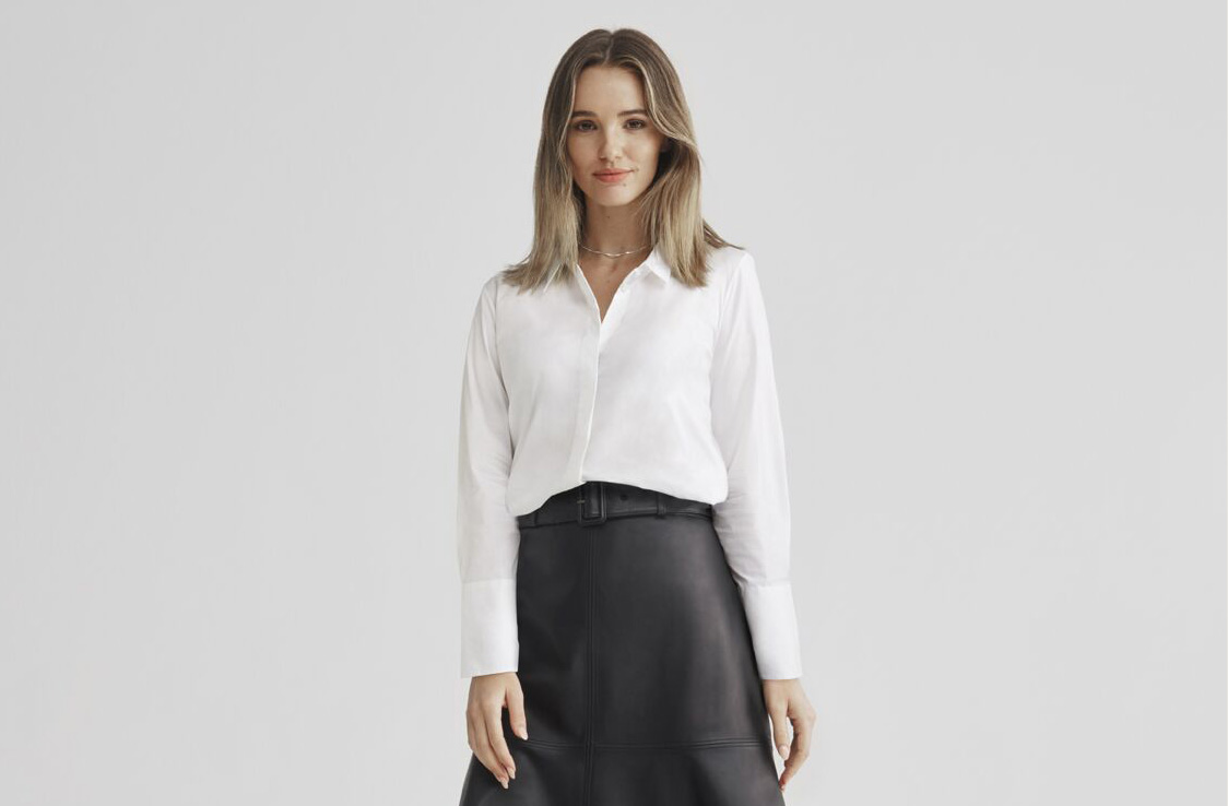 A woman wearing a classy button up white shirt and a leather midi skirt