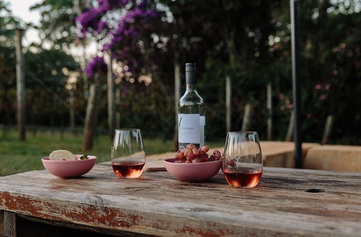 two glasses and a bottle of wine on a table in front of vineyard