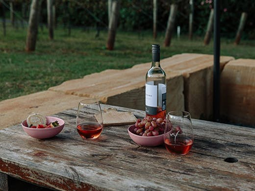 A bottle and two glasses of wine on a bench.