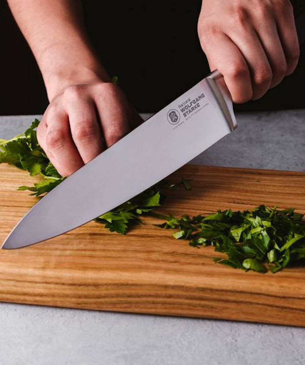 A cook using the Baccarat Wolfgang Stark Chef's Knife