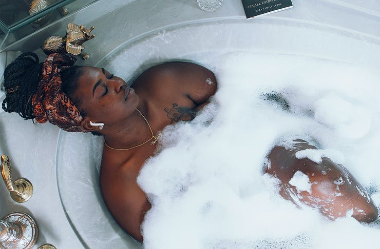 A woman relaxes in a lovely bubble bath.