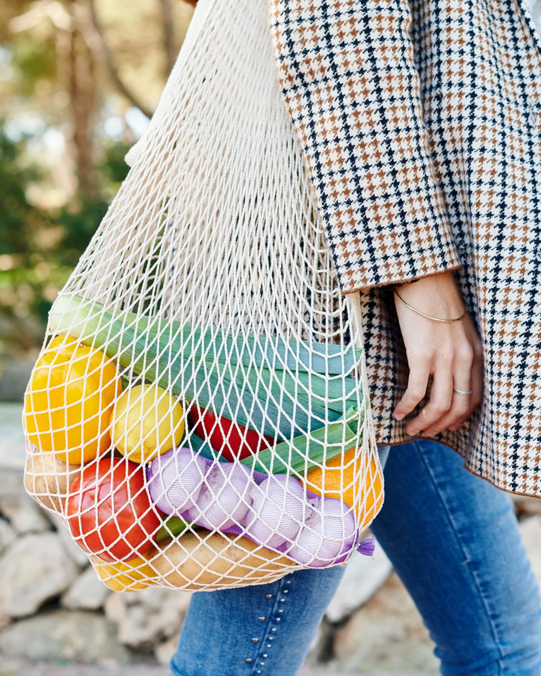 A woman walks with a reusable bag.