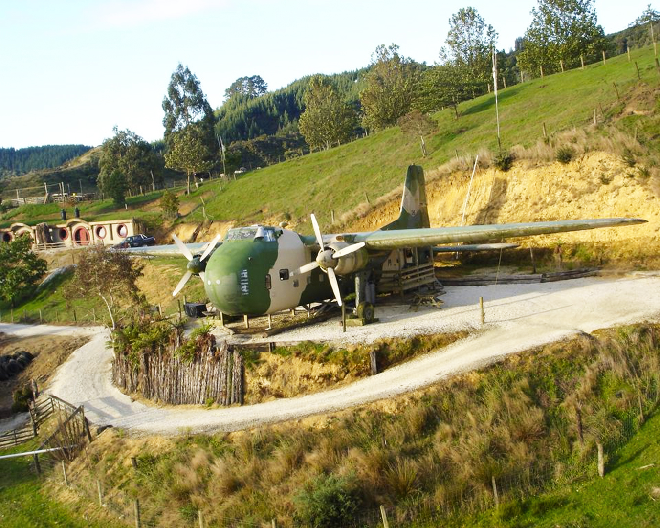A war plane with a hobbit house in the background.