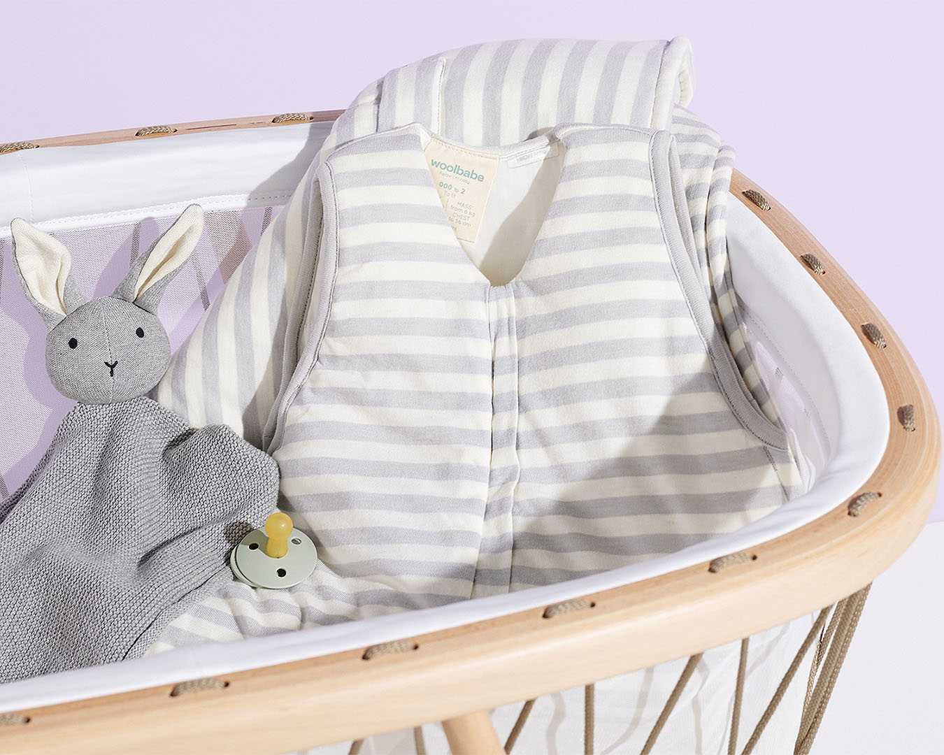 A cot with a sleeping bag babygro and stuffed bunny inside.