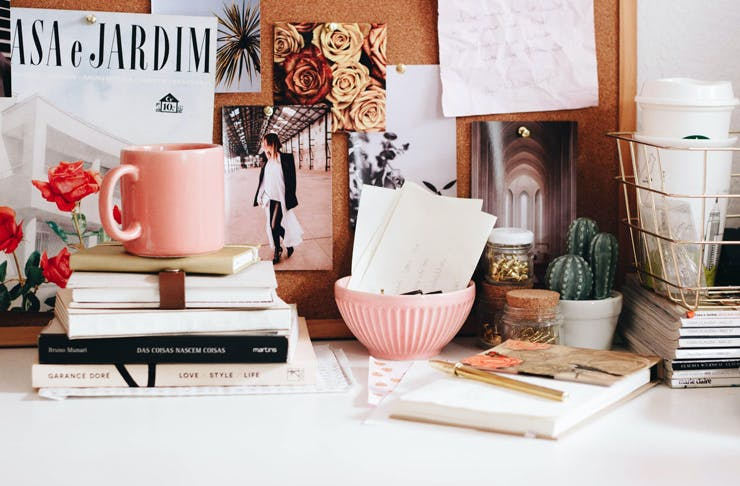A desk with a pink mug, scattered books, and a pin board.