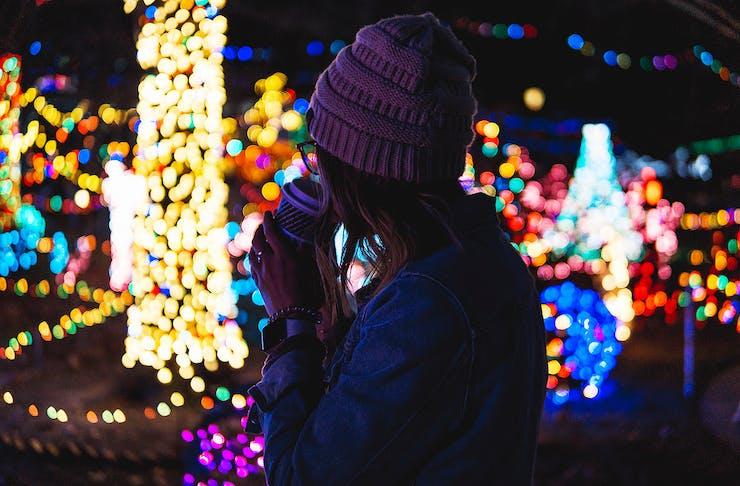 A girl looks at Christmas lights.