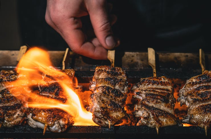 Skewered meat being cooked by the flames of habachi-style grill.