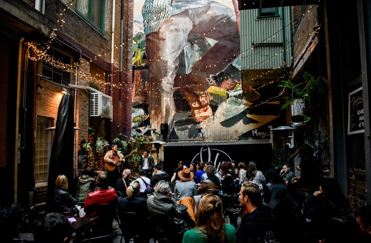 People gathered in a laneway watching live music.