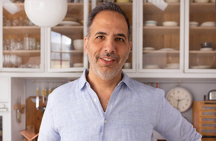 A portrait of chef Yotam Ottolenghi in a kitchen.