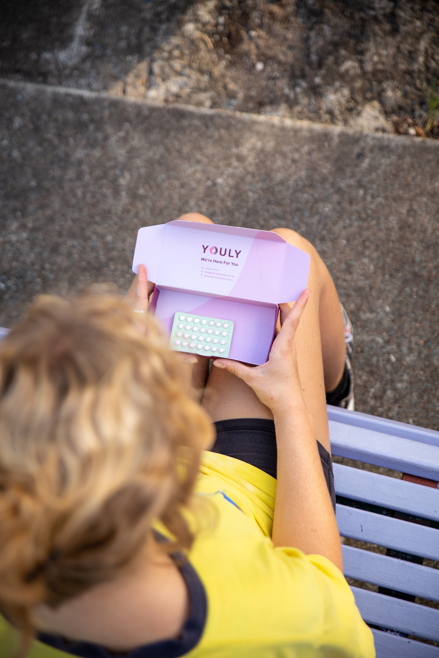 a woman on a bench opening a small box of contraceptive