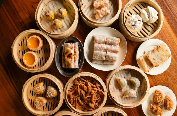 A selection yum cha dishes like pork buns, dumplings and egg rolls in bamboo baskets spread across a table.