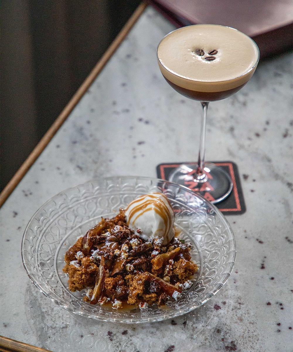 A dessert and espresso martini on a bench