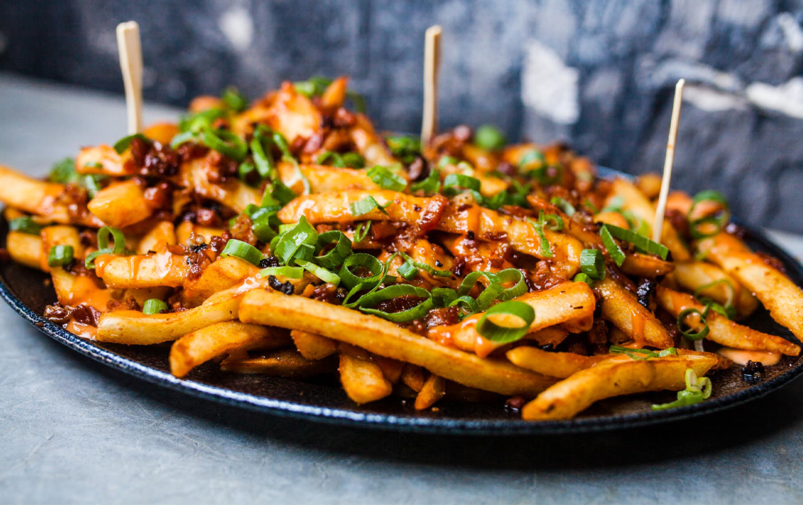 A plate of fries topped with bacon and spring onions