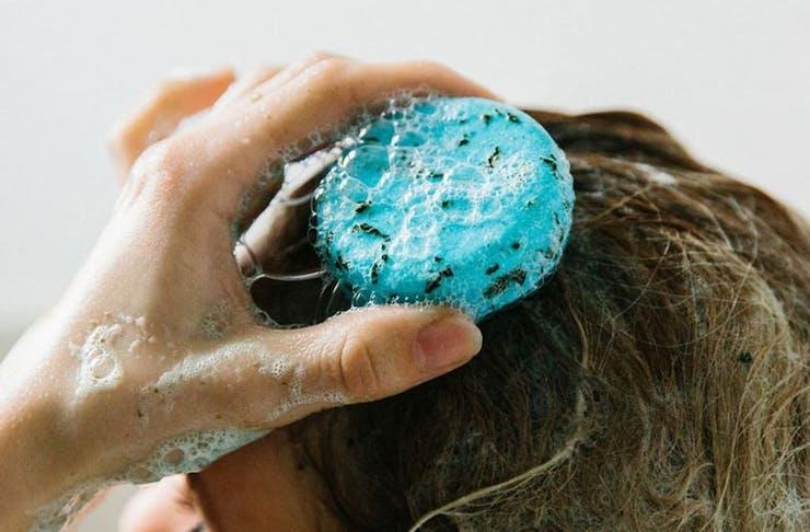 A woman washing her hair with a blue shampoo bar