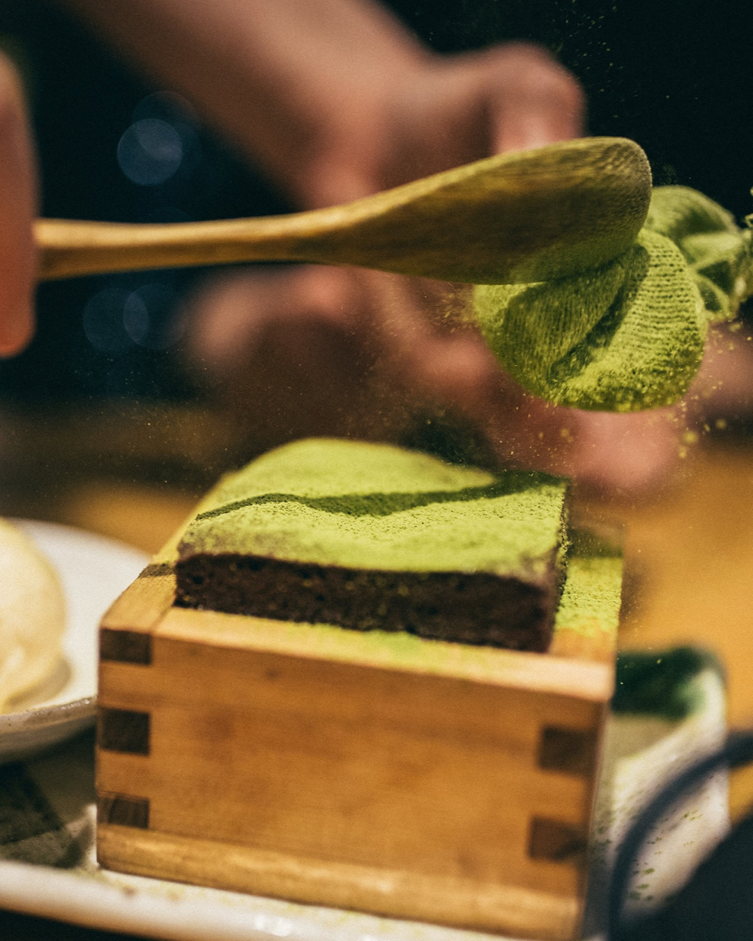 Using a wooden spoon to dust a pudding at Masu with matcha powder