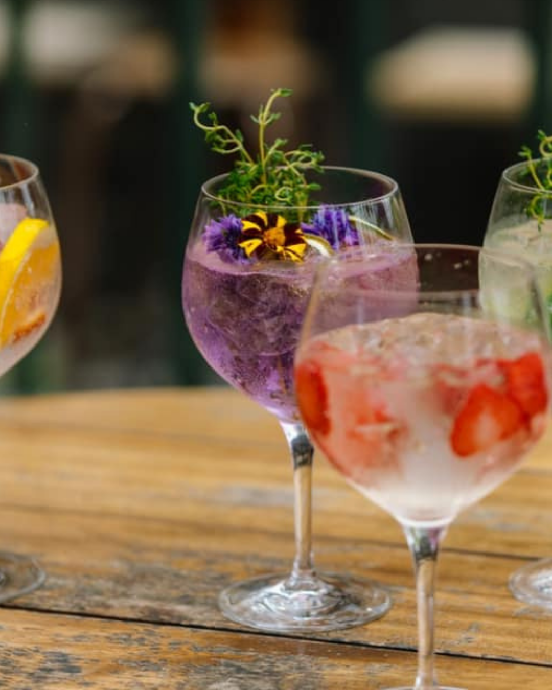 Several wine glasses holding coloured cocktails and flowers