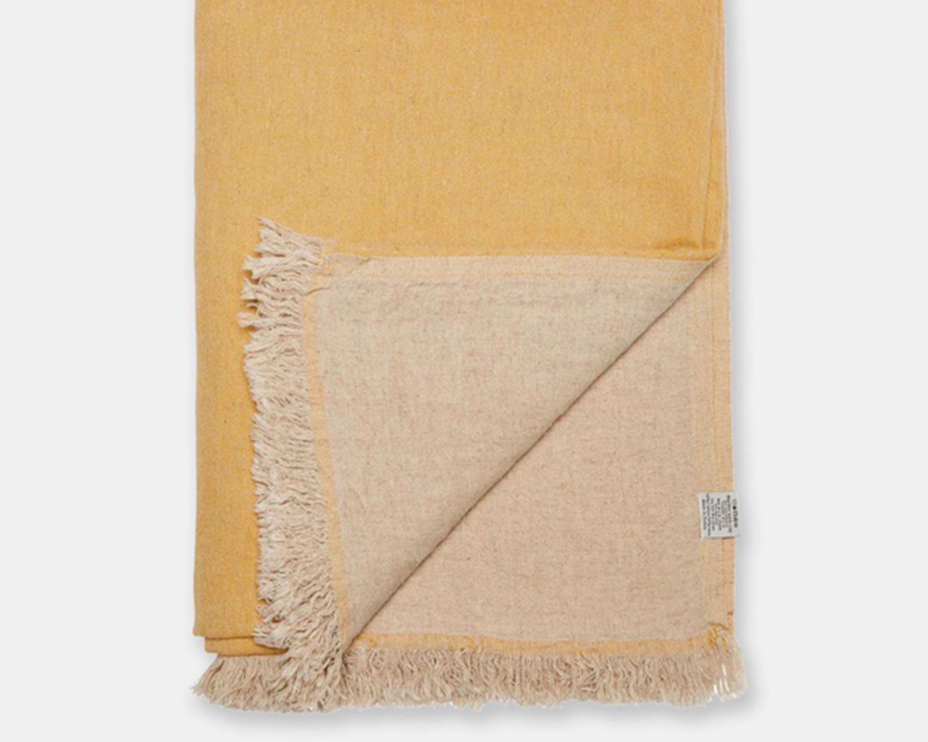 A folded mustard blanket with tassels.
