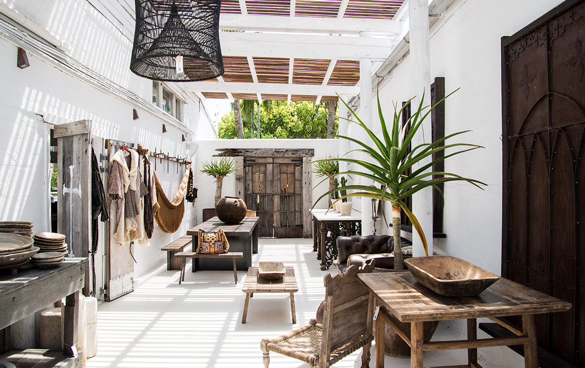 inside a store with white walls and rustic furniture.