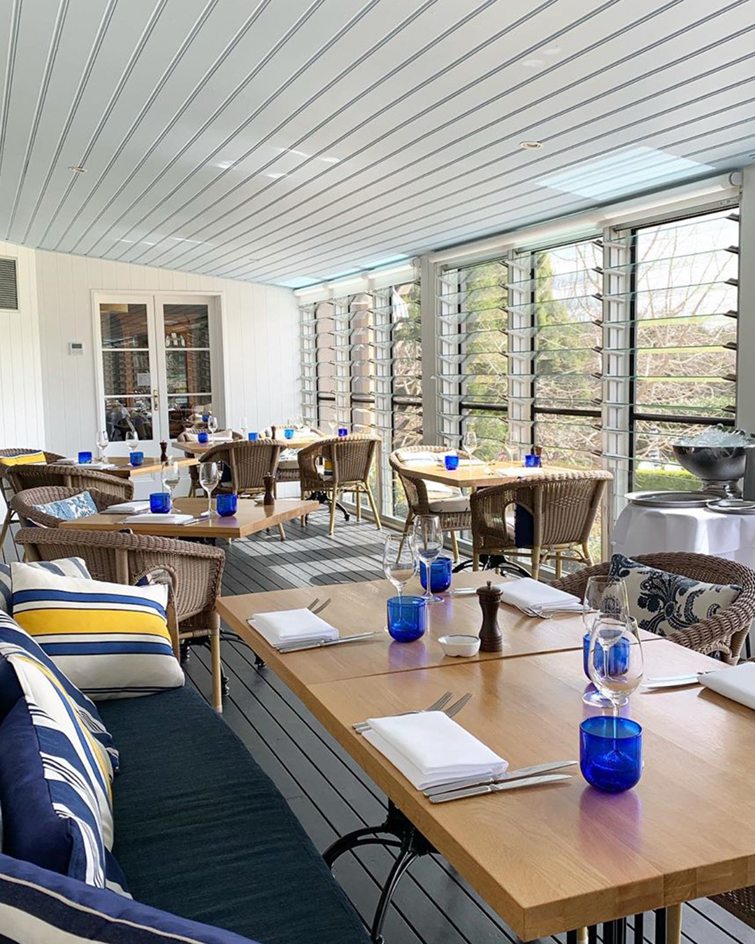 A spacious dining area on the verandah with nautical-style soft furnishings and blue glasses.