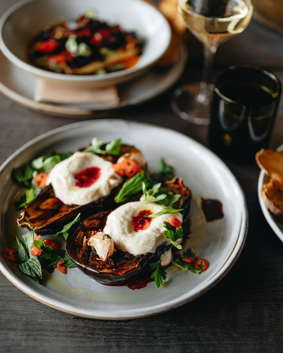 A dish with grilled eggplant, greens and white cheese on top.