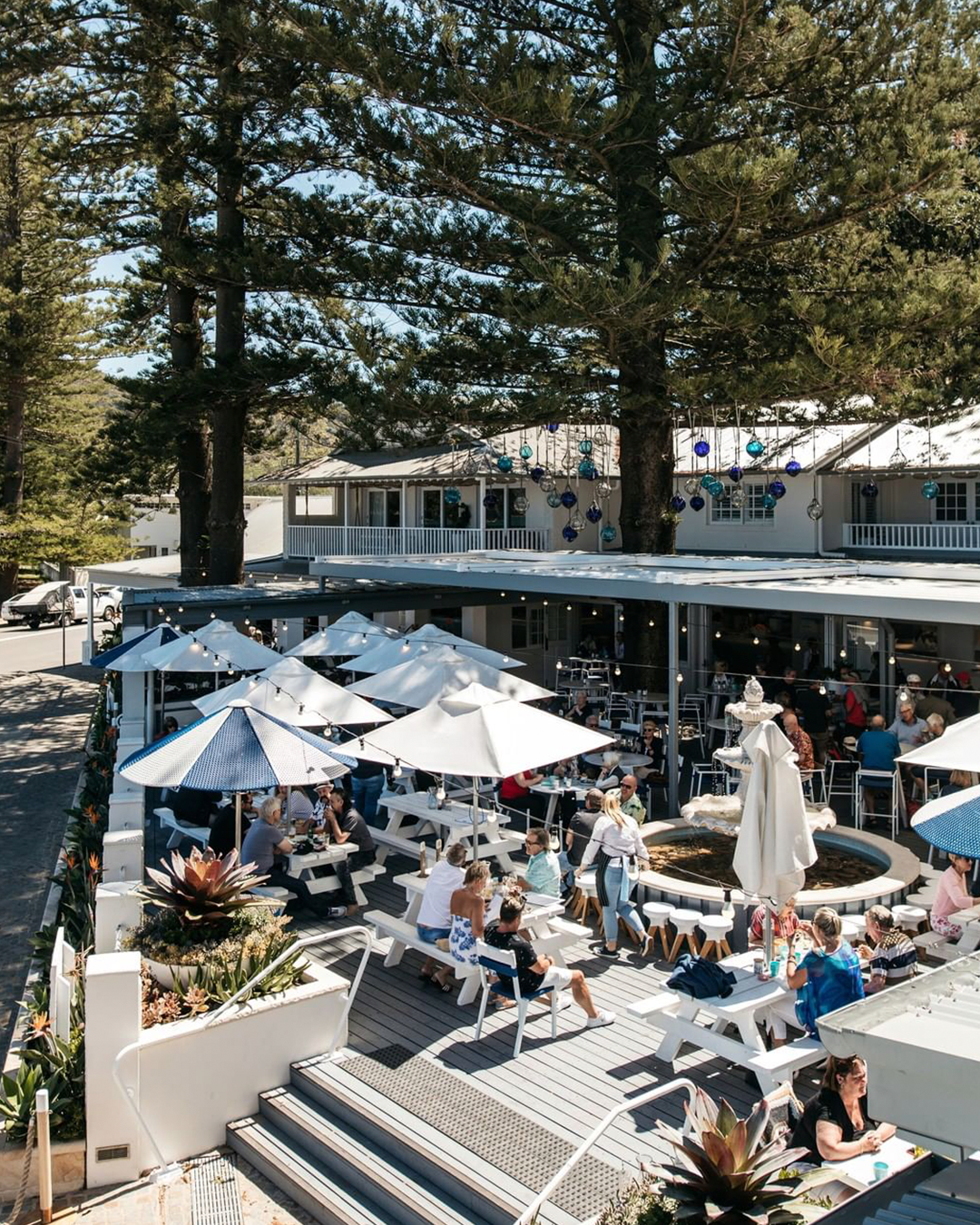 A large pub courtyard with big trees, lots of people and white outdoor furniture.