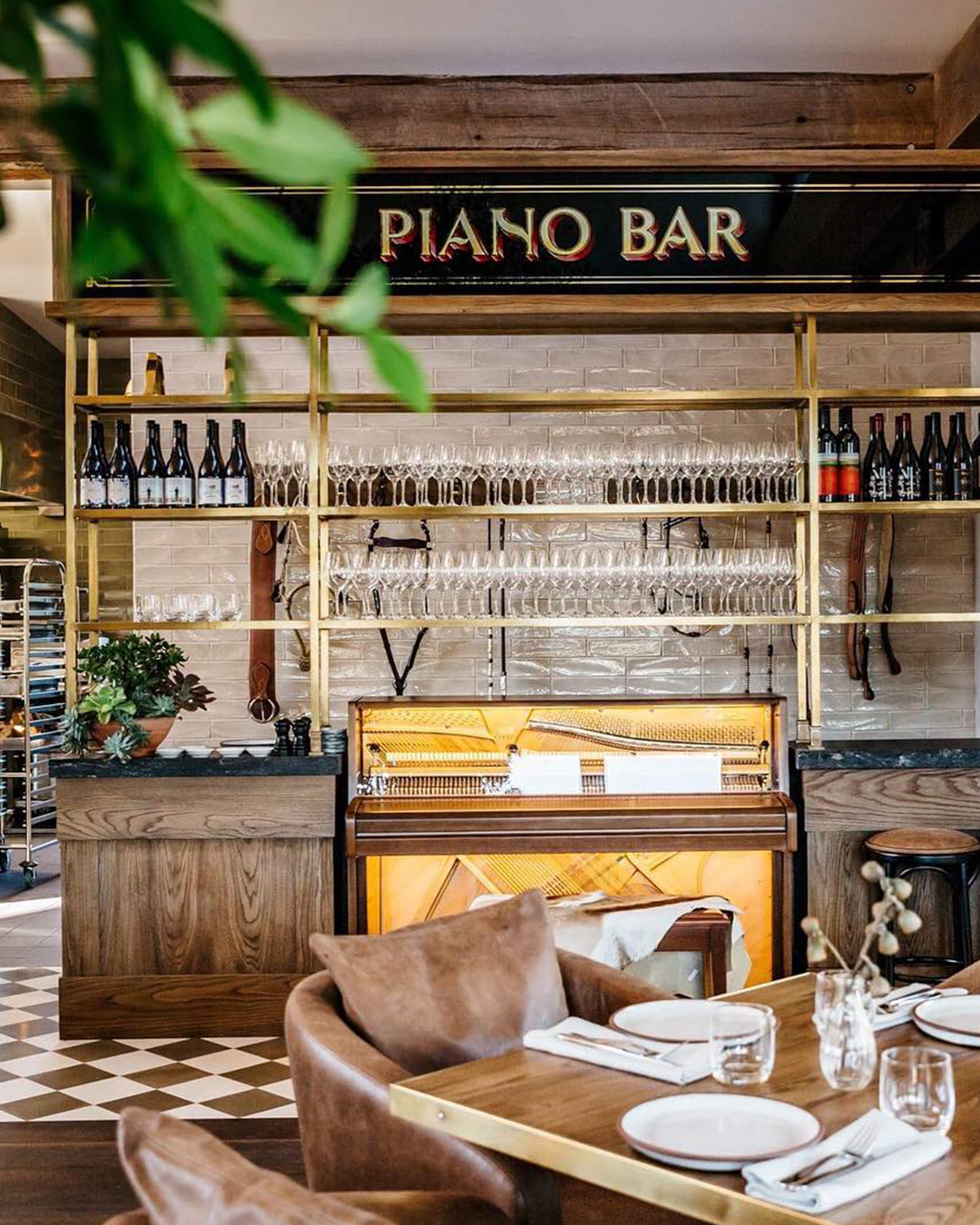 An retro-style piano bar with checked flooring tiles and plush, leather seats around it.