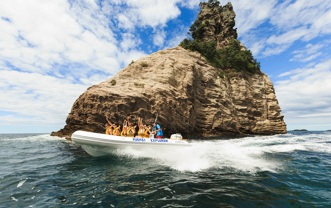 A small boat of people cruise over the water at Cathedral Cove