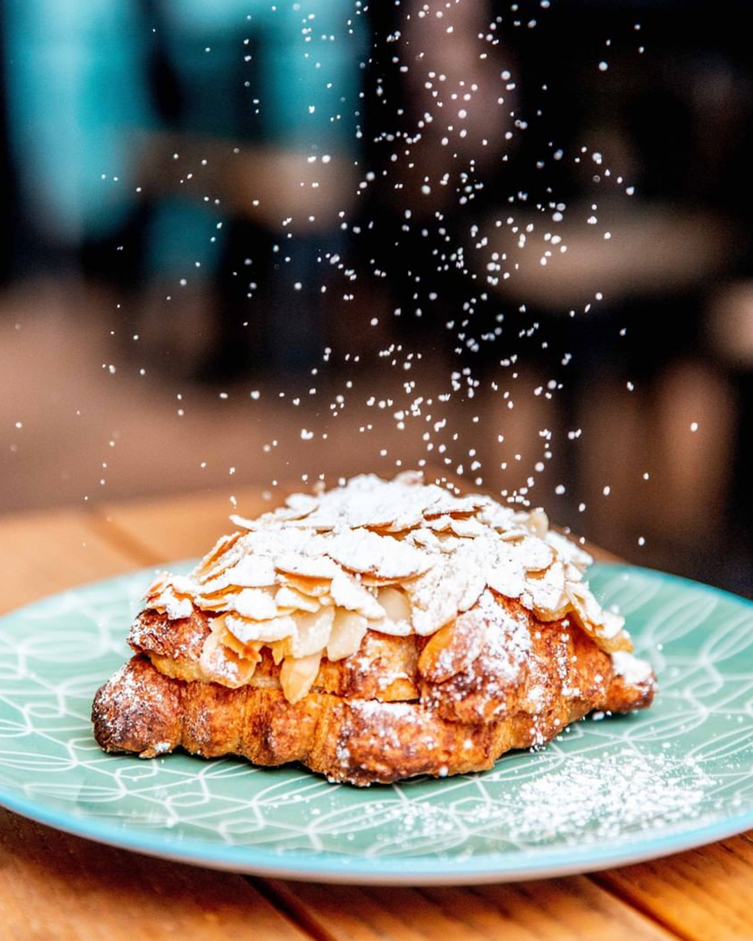 A flaky almond croissant on a plate, topped with almonds and being dusted with icing sugar.