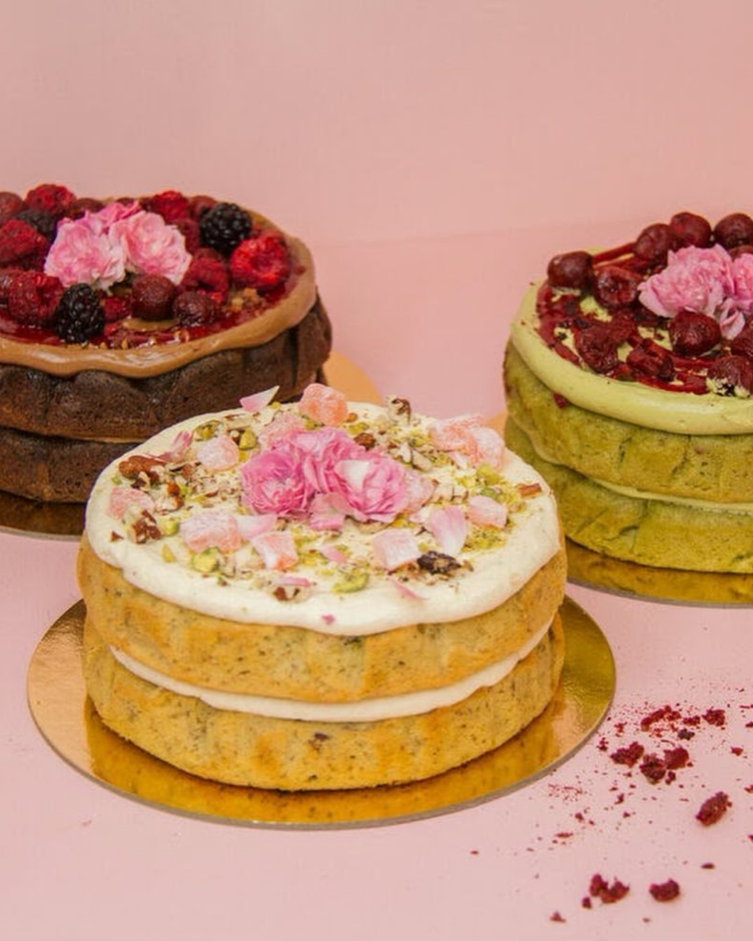 Three gorgeous cakes by The Caker on a pink background