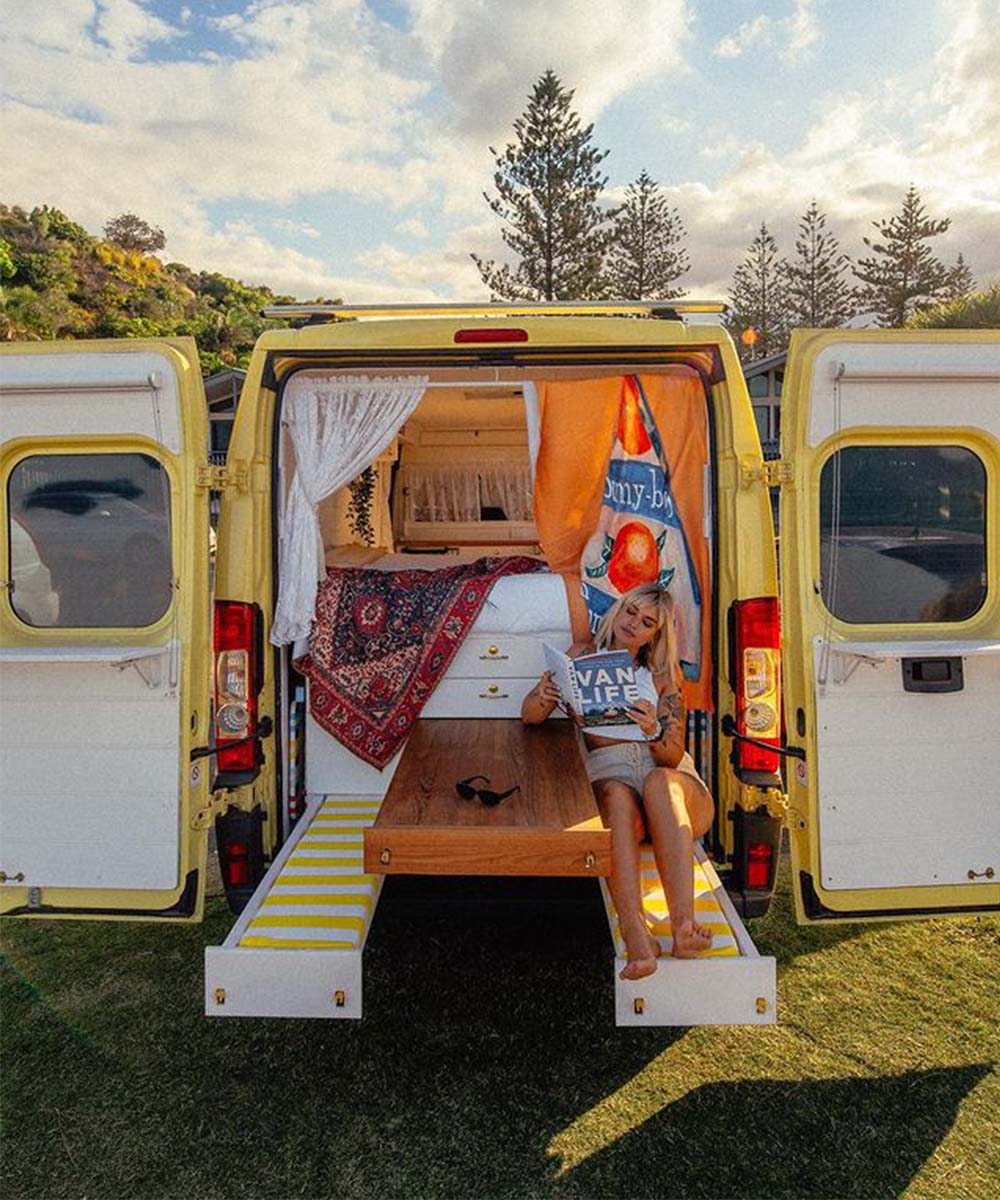 A woman sits in the open back of the Dolce Sole Camper