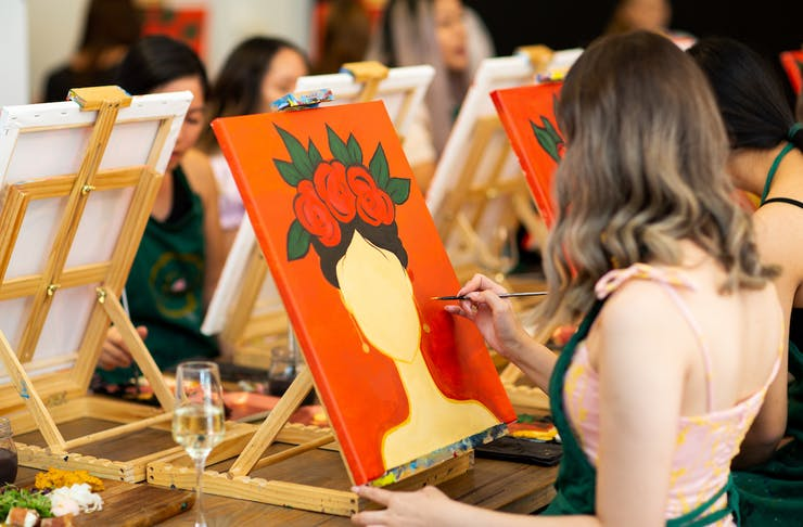 someone painting at a paint and sip class
