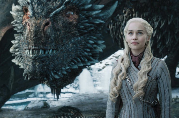 daenerys on set of Game Of Thrones stands in front of a dragon.
