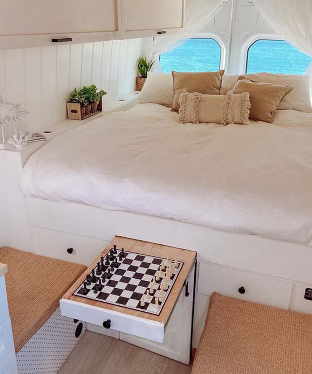 a white bed and chess set feature in the back of the Happy Camper Van