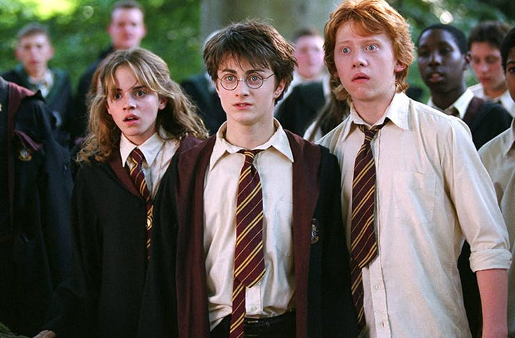 three students standing together looking shocked