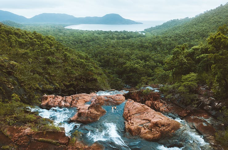 A stunning view over Hinchinbrook Island. Two people swims in the crystal clear waters of Zoe Falls.