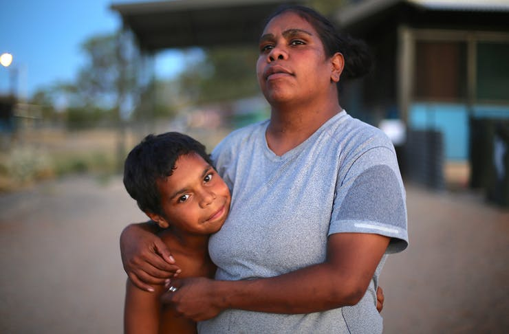 Dujuan and his mother embrace in front of their house.